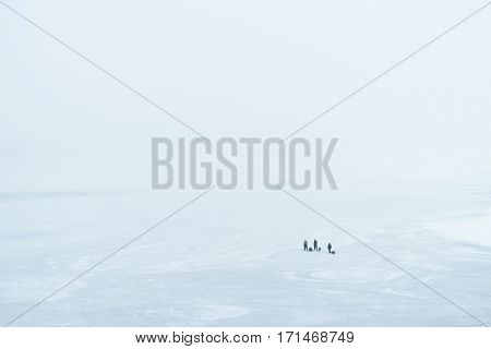 Foggy winter landscape. Top view of a frozen river, and fishermen on the ice. Dnipro river, Kiev, Ukraine