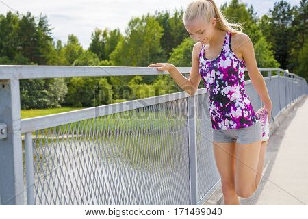 Young fit and smiling blonde woman stretching after stamina workout. Standing on a bridge.
