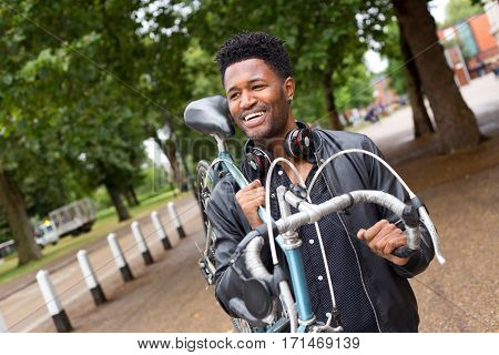 a young man carrying his bike in the street