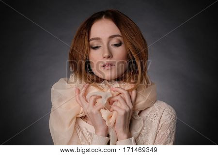 Her hand on the beige scarf, eyes lowered, sight directed downwards. Close-up, isolated, warm colors.