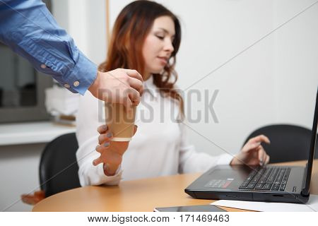 Man brought coffee for woman sittng at desk in office