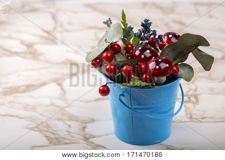 Flowerpot decoration with natural green plant and flowers and artificial mushrooms on table