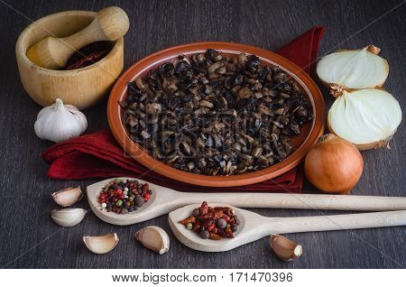 Roasted mushrooms with spices on a plate, wooden background