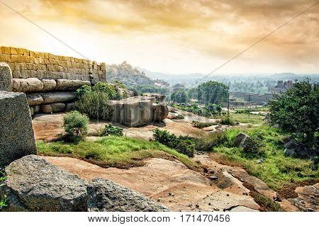 View of Prasanna Narasimha Temple from the Hemakuta Hill at sunset. Ancient ruins of Vijayanagara Empire in Hampi, Karnataka, India.