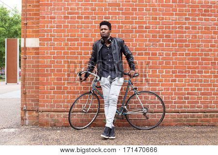a young man with his bike leaning against a wall