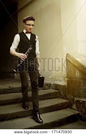 Stylish Hipster Man Holding Clarinet And Walking With Case On Background Of Old City