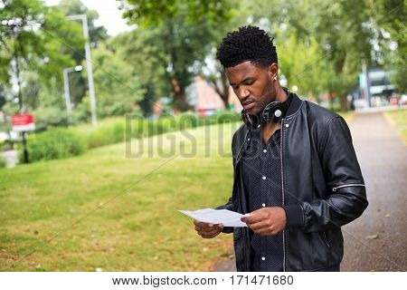 a young man reading a letter outdoors