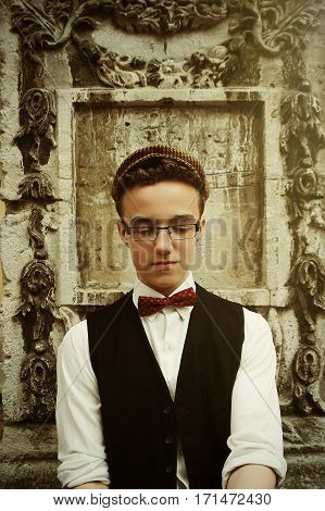Stylish Hipster Man Wearing Glasses And Tweed Hat, Being Confident And Calm, On Background Of Old Ci