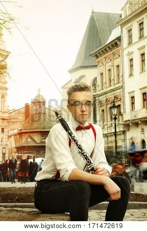 Stylish Hipster Man Sitting And Holding Clarinet In Old Center Of Europe City Lviv