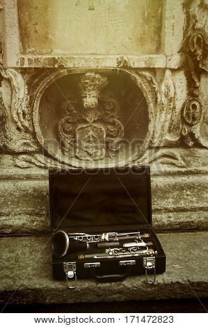 beautiful black and silver clarinet in classic case on background of old city space for text