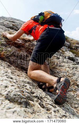 Guy trying climb mountain with backpack on his back