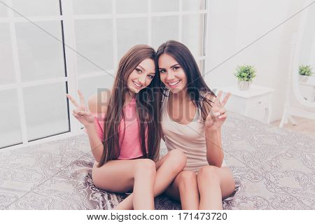 Two Pretty Smiling Girls In Pajamas Gesturing V-sign