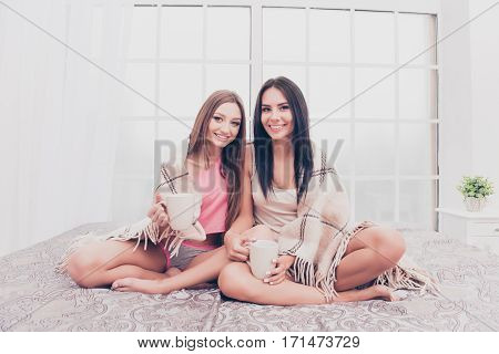 Two Sisters Sitting On Bed And Basking With Plaid And Coffee