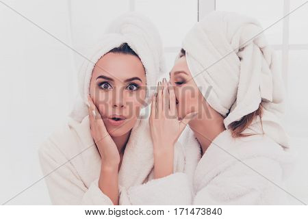 Portrait Of Young Girl In Bathrobe Telling Secret To Her Shocked Sister