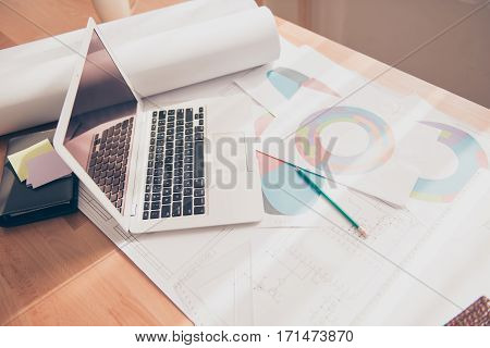 Photo of working place of engineer with blueprint diagramas and laptop
