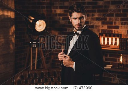 Serious Bearded Handsome Young Man  Touching His Black Suit