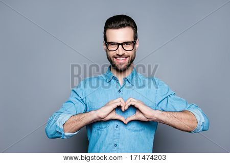 Portrait Of Happy Handsome Man In Glasses Making Heart With Fingers