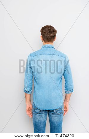 Back view of a young casual man isolated on gray background