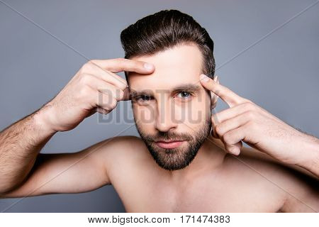 Portrait Of Young Man Looking For Acnes On His Face