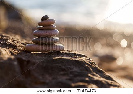 Pyramid of pebbles on sea coast in summer in afternoon