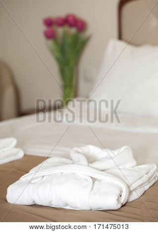 hotel room with white bathrobe on the bed