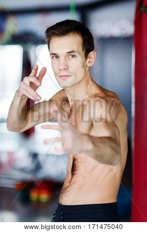 Portrait of topless young man in gym