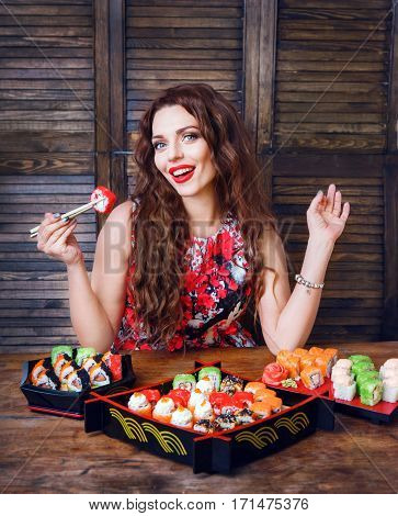 Young woman holding sushi with a chopsticks. Woman eating sushi