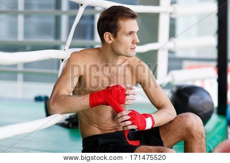 Young sportsman on background of fight ringside with boxing bandages