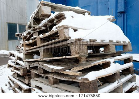 Old wooden pallets and snow. Winter industrial landcape.