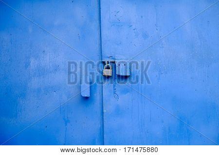 Big metal door blue dark paint and dark lock.