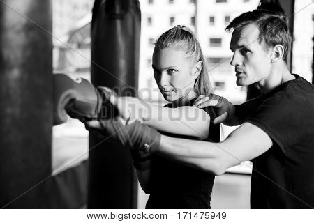 Black-white photo of girl workout with coach in gym