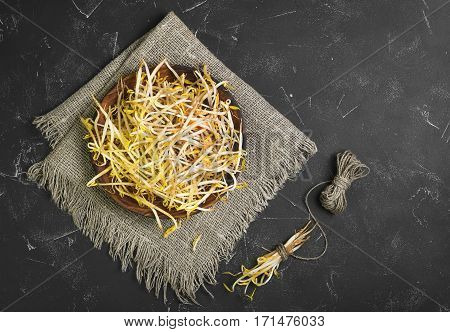 Bean sprouts in the wooden plate on sackcloth. Mungbean Sprouts in bundle tied vervevkoy. Dark black concrete background. Top view from above and copy space.