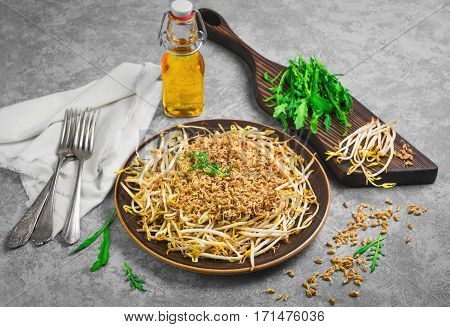 Food vegan salad from sprouted wheat grain and sprouted beans. Olive oil for salad. Sprouted wheat on gray concrete background table sprouted beans on wooden board cloth arugula forks.