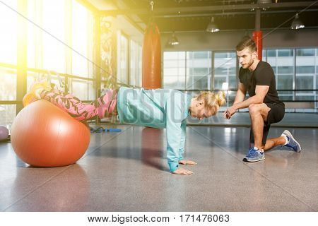 Fitness woman on fitball in sports hall with coach