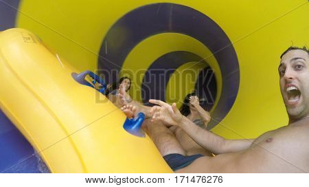 Friends having fun and sliding down in a colorful water slide