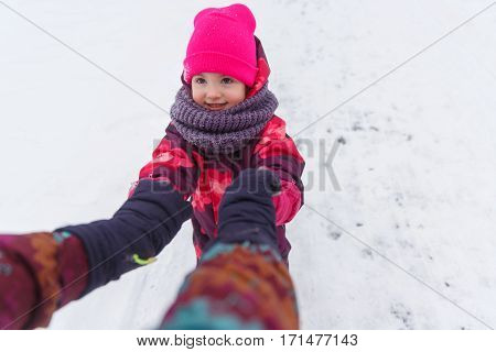Stroll young mother with small daughter in winter