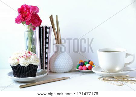 Chic and beautiful desktop with cupcake, flowers, office supplies, coffee and gumballs. Wall space for copy.