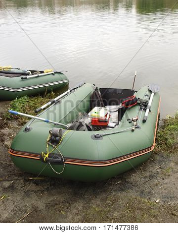 Rubber boat with gear for fishing fishing rods autumn river close up