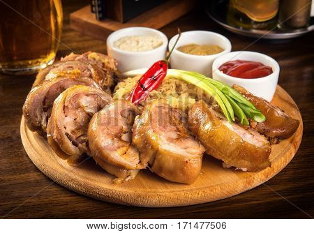 Roasted Pork Roulade with boiled cabbage and sauces on wooden tray.