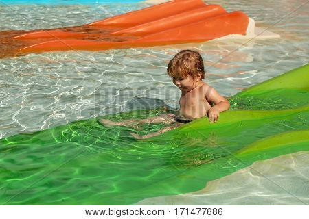 Happy cute baby boy with blond hair slides from green waterslide in outdoor pool on sunny summer day on water background
