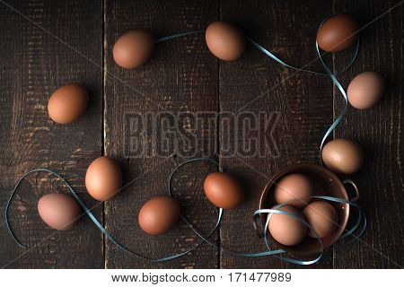 Chicken eggs with ribbons on the wooden table top view