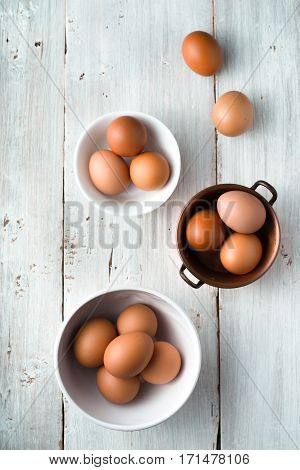 Bowls with chicken eggs on the white wooden table top view