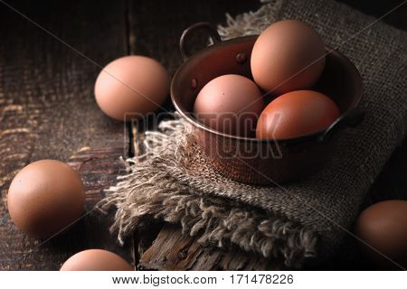 Chicken eggs in the cooper pot on the wooden table horizontal