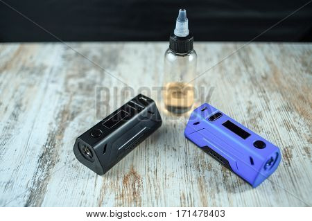 Electronic Cigarette Mod And A Jar With Fluid. Ends. Top View.
