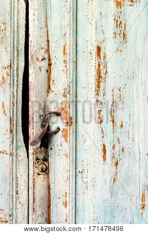 Aged pierced door and with padlock for background