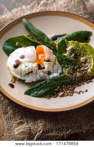 Poached egg with avocado cream sauce and spinach on the ceramic plate vertical