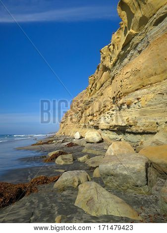 View down Torrey Pines State Reserve beach, with cliffs, sea, rocks and blue sky, copy space