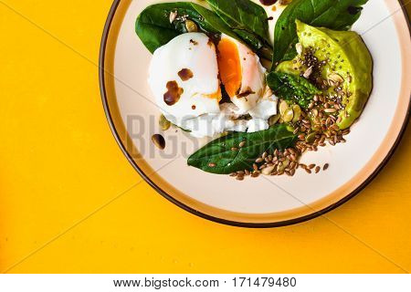 Poached egg with avocado cream and spinach on the yellow background top view
