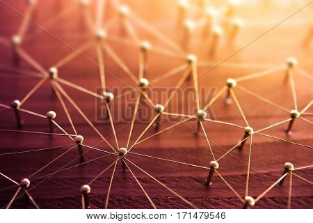 Linking entities. Network, social media, internet communication abstract. People or machines connected by communication network. Web of gold wires on rustic wood.  Shallow DOF. Strong highlight.