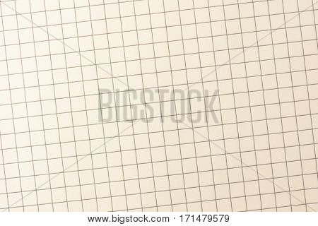 Graph paper intentionally shot slightly diagonally, for more rapid or active feel. incandescent lighting tone. highlight on upper left.